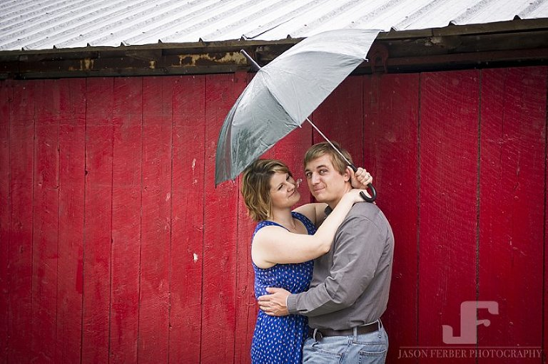 Engaged couple in front of red barn door with umbrella